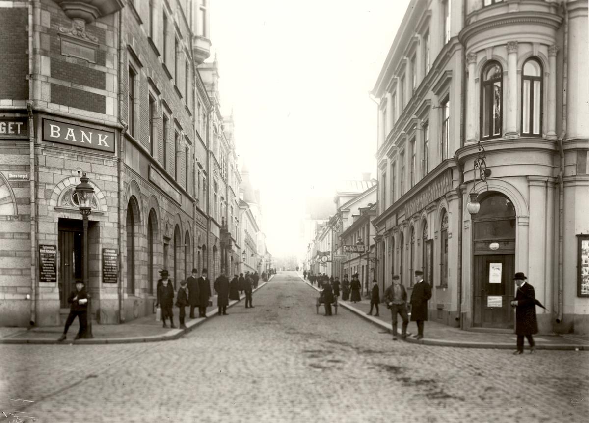 Orig. text: Storgatan från Stora Torget mot Borggården.Sydsvenska Kredit Aktiebolaget vänster i bild och Sahlströms bokhandel till höger.