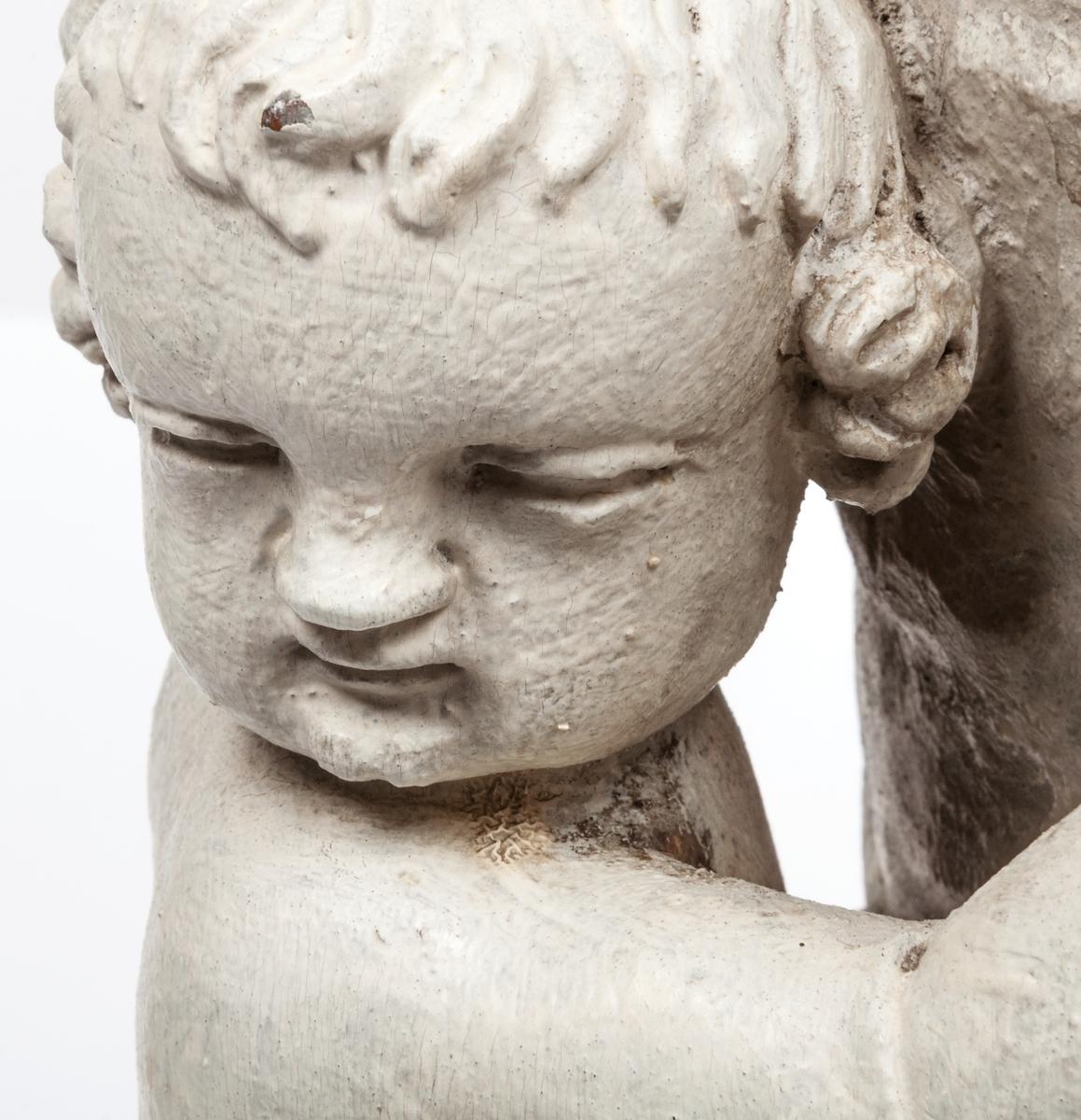 Kyrklig skulptur, trä, staty från gamla korskranket i Heliga Trefaldighets kyrka i Gävle, av Ewert Friis omkring 1665.   Stående kvinnofigur med naket barn på vänster arm samt stående naket barn vid höger sida. Sistnämnda barn har ett brinnande hjärta i höger hand och kvinnans vänstra hand på sitt huvud. Vänster ben är främst, foten avslagen. Sittande barnets ena ben och andra fot avslagna.  Fyrsidigt, profilerat postament.  Gråvit färg.