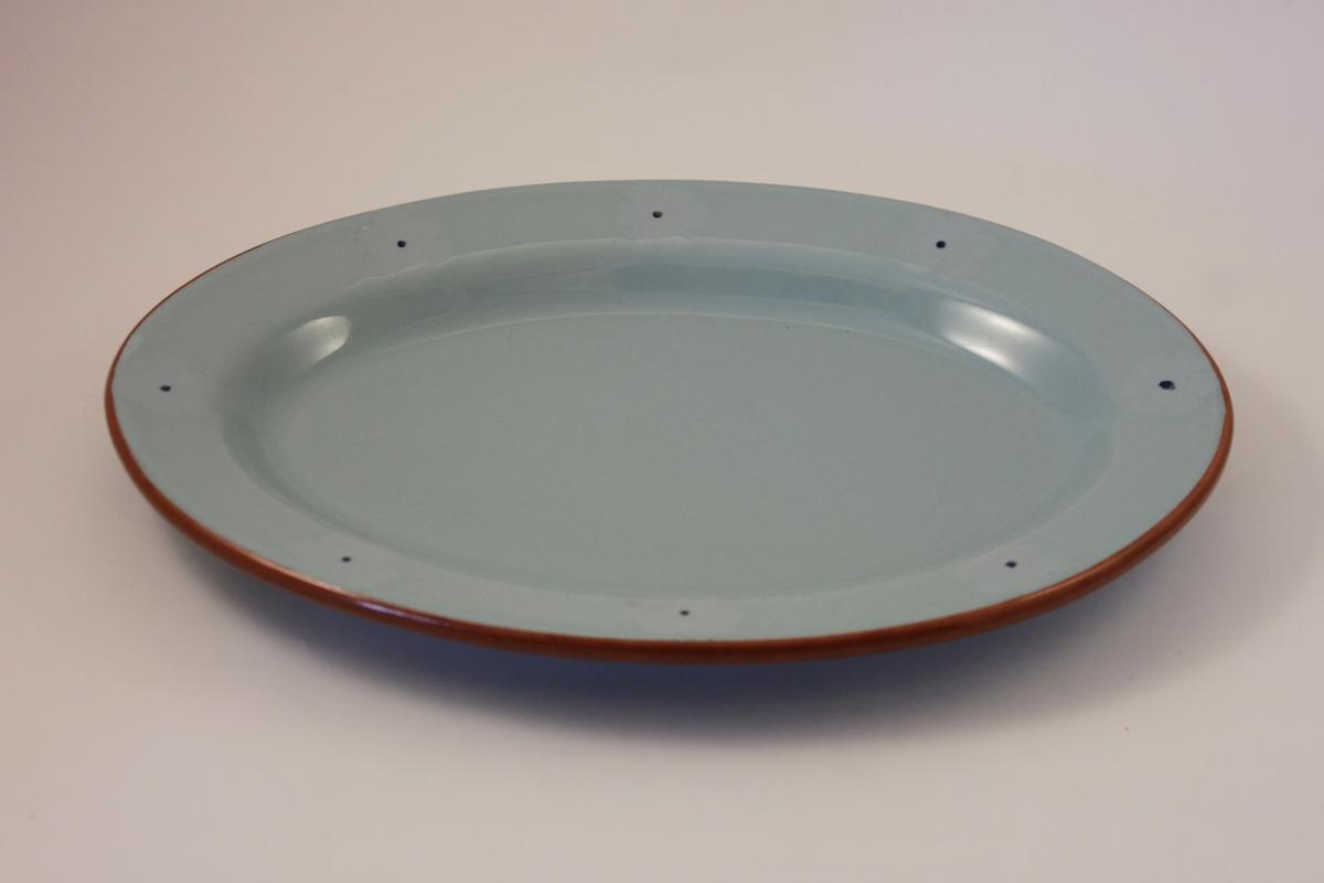 Turkosblått, ovalt uppläggningsfat i glaserad keramik. Brun kant samt blå prickar kring brättet som ursprungligen varit mitt på små blommor som förlorat sin färg.