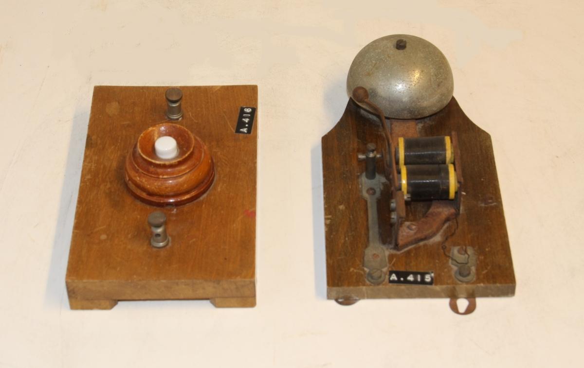 Ringeklokke og knapp. 2 delar, Ringeklokke med spole merka A.415 reg nr ØM.03550-A Knapp med tilkobling for ledning. merka A.416 reg nr ØM.03550-B. Begge delane er montert på kvar si plate av tre.