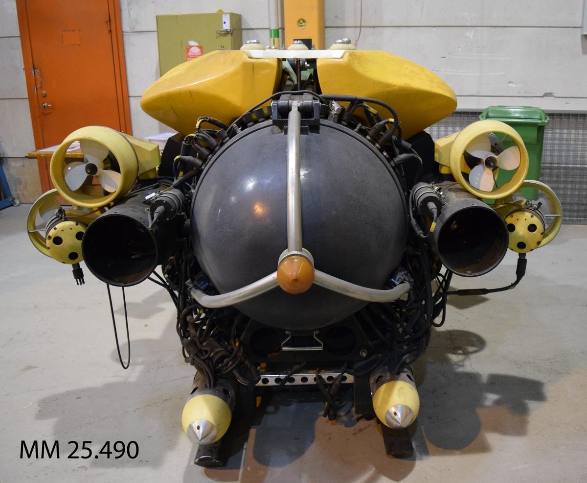 Undervattensfarkost målad i huvudsak i gult och svart. MÄrkt MANTIS 010 VICTORIA på överdelen. Den trycksäkra delen består av en tub med rundade ändar i vilken besättningsmannen ligger på mage och framför farkosten. I fören en stor rund glasruta och två armar i metall med gripklor. Propellrar i dysor runt om farkosten för framföring. I akterna en lucka som en halvsfär.