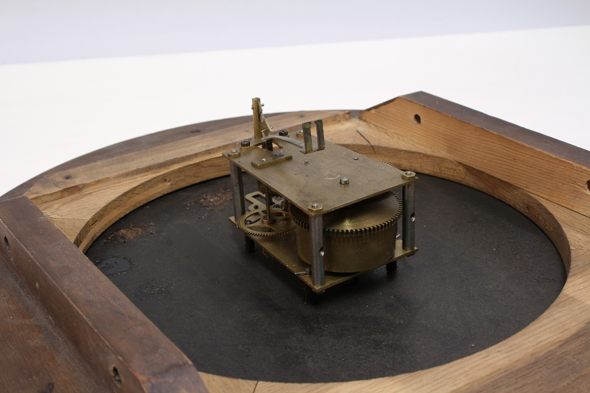 Uret har hvit tallskive med romertall med glass i åttekantet eikekasse. Rammens indre sirkel er kantet med gull.