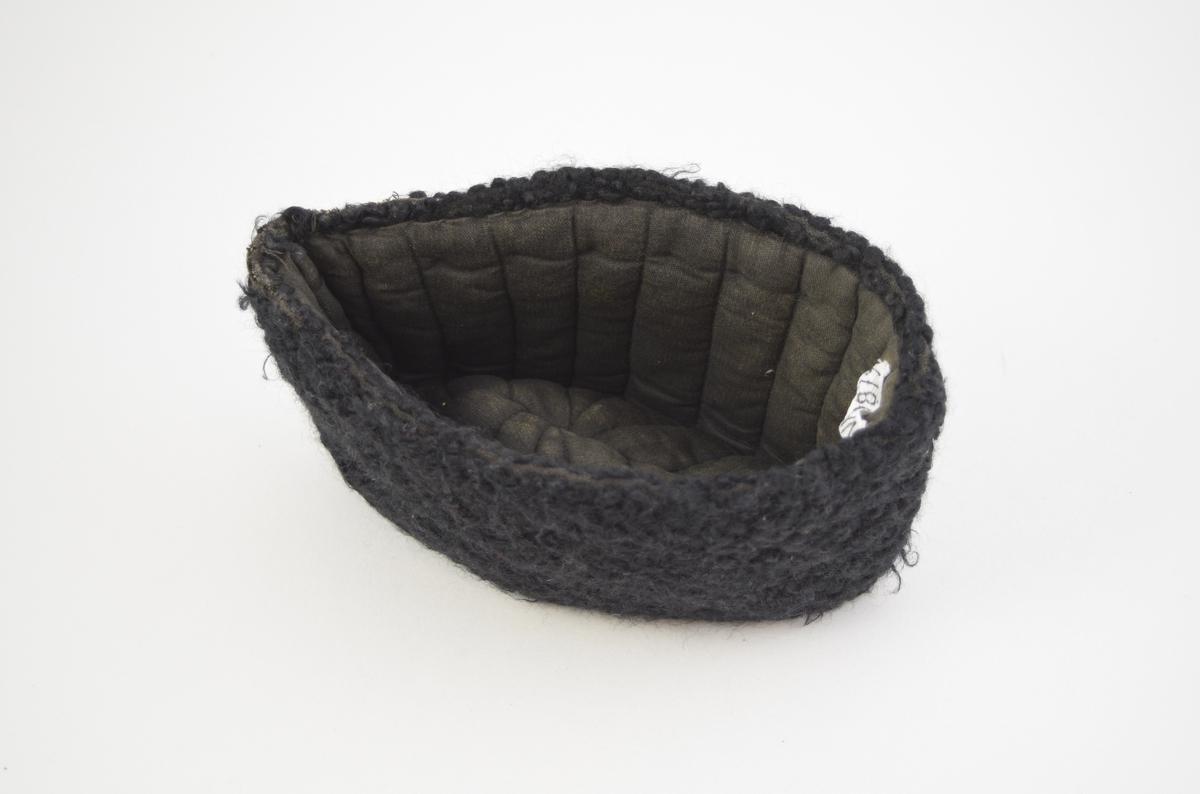 Lue med tykk sort ull på utsiden, foret med ullstoff sydd med kanaler.