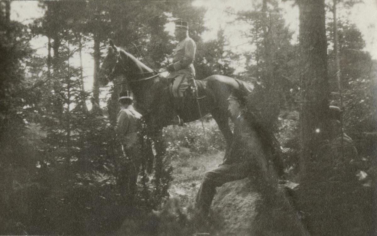 En officerare på häst samt en grupp soldater i skogen.