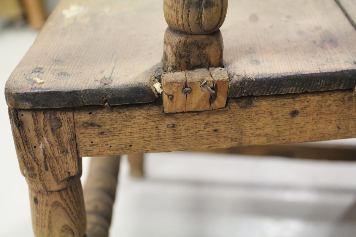 Stol i furu og eik. Fire loddrette ben. Bakbenene firkantede, forbenene er sammensatt av tre firkantede ledd adskilt av sylindirske partier som ved vannrette innsnitt er delt i fire. Til sammen syv bindingsbretter, to på hver side og to bak. Disse er alle firkantede. En frontsprosse som er rund og ved innsnitt er delt i kulelignende ledd. Smal, glatt sarg, trapesformet sete dekket av trefjeler. Armlen dannes av en arm som ytterst er svinget litt oppover og ender i en nedkrøllet tupp. Armelenet bæres av en loddrett, kuledelt støtte som er anbragt litt innenfor forbenet.