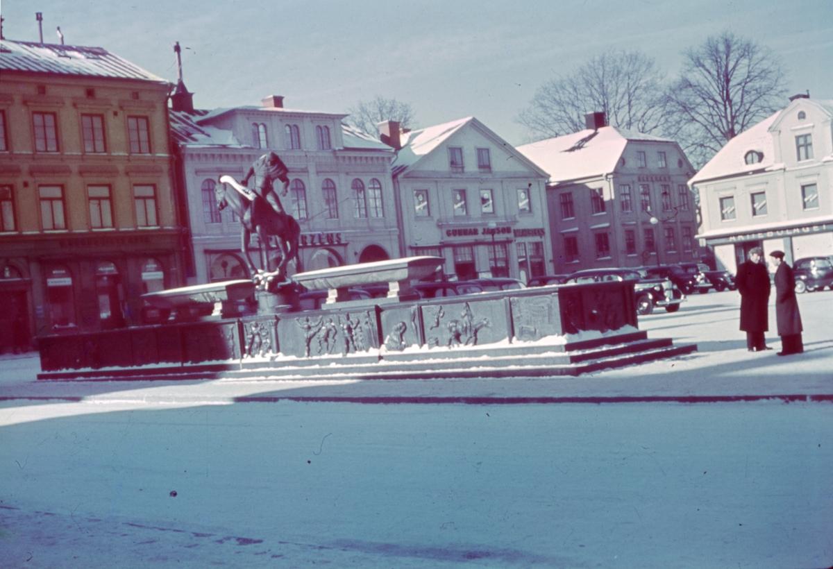 Stora Torget sedd mot nordväst från Storgatan med Folkungabrunnen i förgrunden. Folkungabrunnen med Folke Filbyter, skulpturen uppförd av Carl Milles, invigdes 1927. Inspirationskälla till detta verk var Verner von Heidenstams roman Folkungaträdet, där Folkungaättens undergång skildras. Folke Filbyter - ättens stamfader - avbildas, när han till häst letar efter sin bortrövade sonson. Det 16 meter långa brunnskaret i svart granit, fungerande som en barriär mellan torget och gatan, återger med sina reliefer episoder ur Folkungatidens historia.