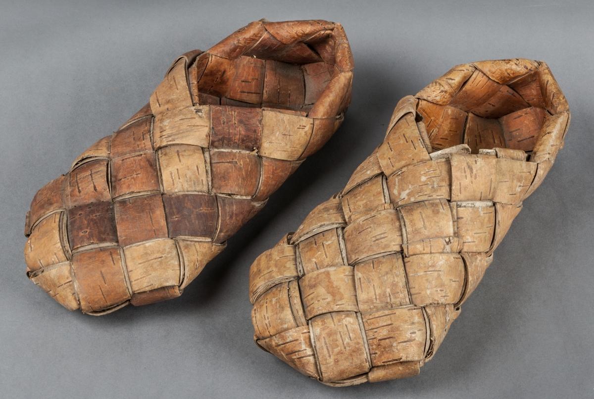 1 par näverskor, flätade med diagonal flätning som enligt tradition är en finsk teknik. Skorna är använda då de är något slitna på undersidan.