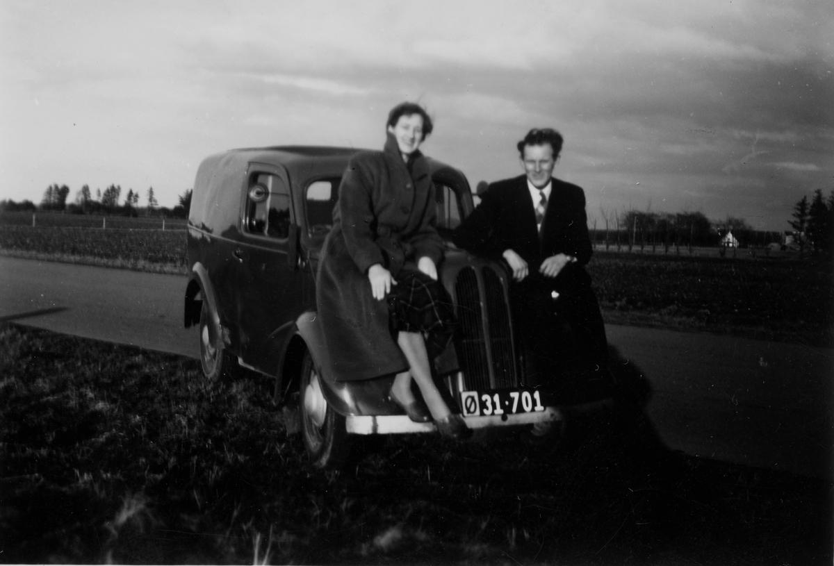 Par poserer foran bilen til Mathis Henriksen. Bilen er av det russiske merket Moskvitch og er en modell i 400-serien. Denne serien ble produsert mellom 1947-1956.