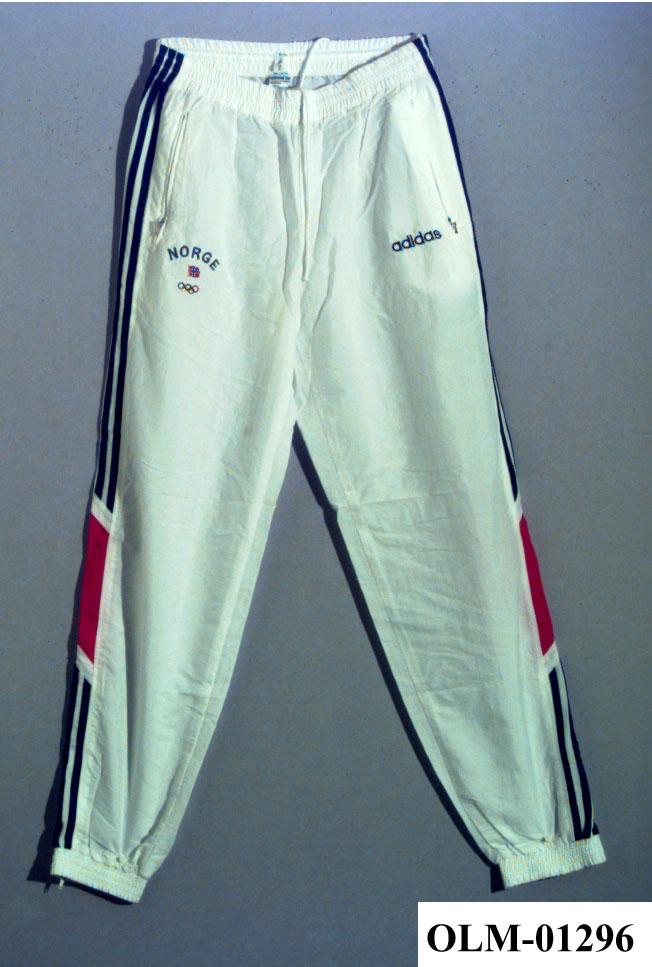 021ac7b0 Hvit treningsbukse med striper i rødt og blått på ytterside av hvert ben.  På høyre