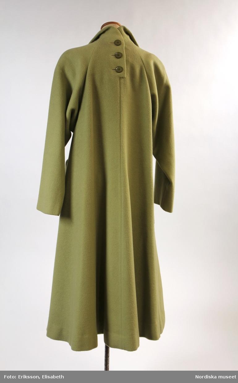 """Kappa av ylletyg från 1953. Kappan, klänningen och handskarna är använda av fru Maja Upmark, Stockholm, 46 år. /Utställningstext """"Mitt 50-tal"""" 2017"""