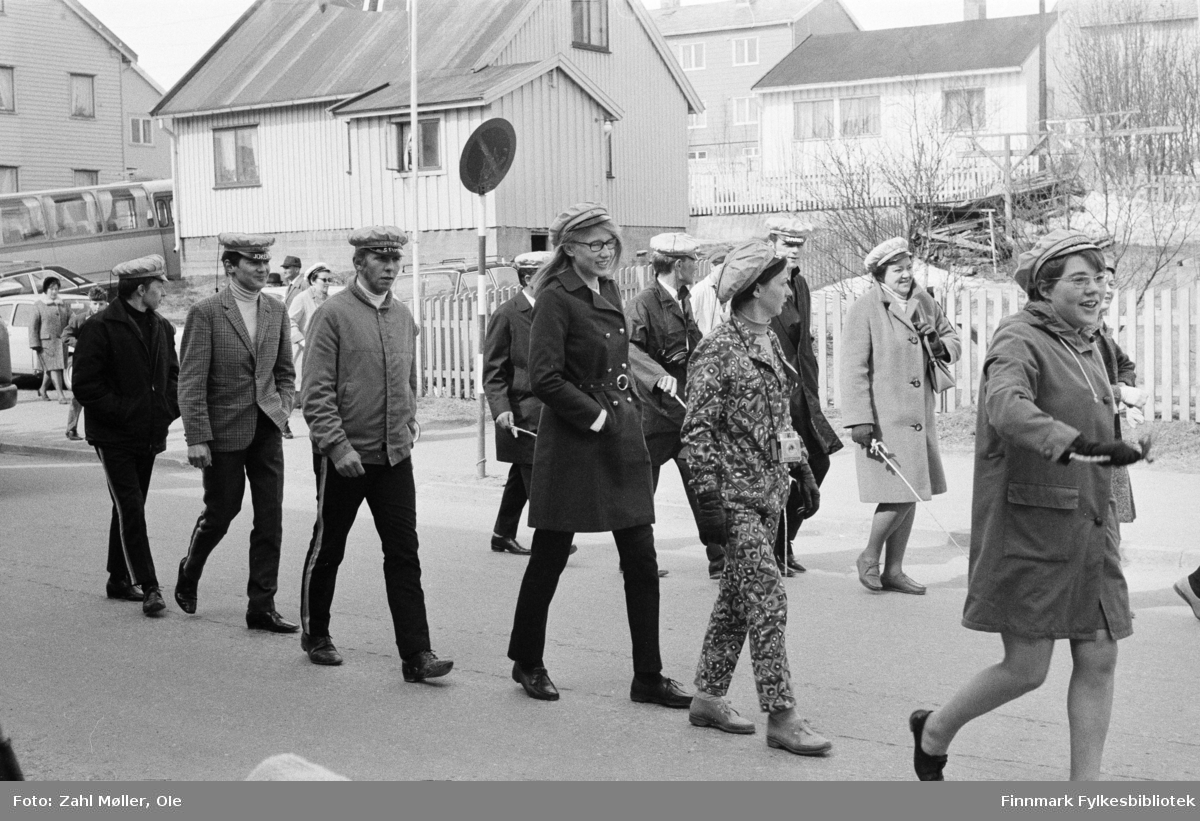Vadsø 17.5.1969. Fotoserie av Vadsø-fotografen Ole Zahl-Mölö. Russen passerer i russetoget. Legg merke til den moteriktige  damen med fargerik bukse og jakke - og polaroidkamera rundt halsen!