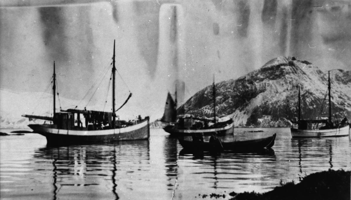 Fiskebåter ute på sjøen. To menn ror en færing ut til en av båtene.