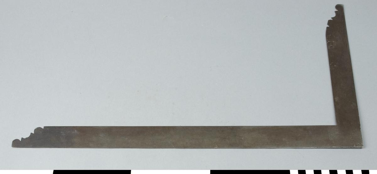 En vinkel i utförande som en plåtslagarvinkel. Den är av stål och tillverkad i ett stycke och polerad. Båda skänklarnas ändar är profilerade i dekorativt syfte. De är tunna och böjliga samt jämntjocka. Saknar måttgradering. Stämplad 18.  Funktion: Markering av 90º vinkel på arbetsstycke