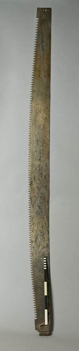 Timmersåg av stål. Text: SANDVIKENS JERNVERKS AB SANDVIKEN SVERIGE, EXTRA PRIMA GARANTI, No 225 EXTRA TUNNSLIPAD I RYGGEN.  Funktion: Tvåmansverktyg för trädfällning
