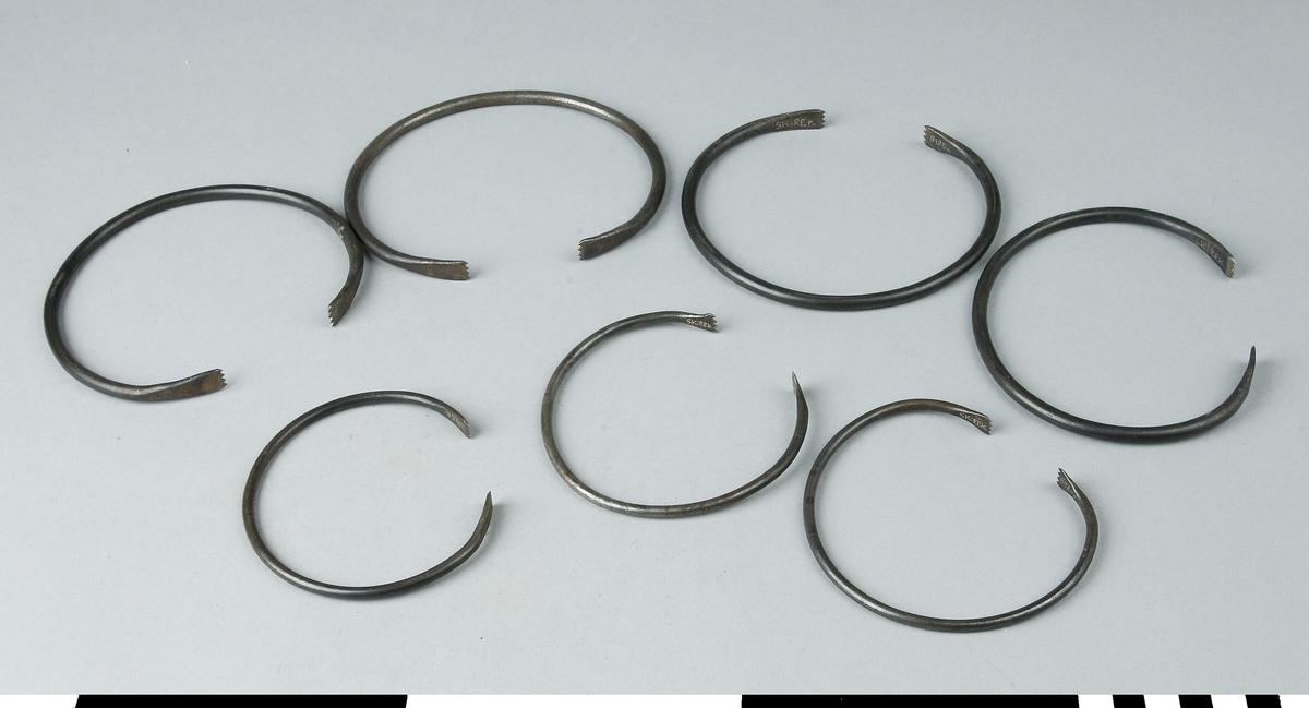 Spännbåge, 7 st av stål. Spännbågen består av ett runt stål med diametter 6 mm som är format till en öppen cirkel med en öppning på ca 40 mm. Spännbågens båda ändar har en taggig kloliknande avslutning. Spännbågen är avsedd att spänna runt hörn vid limning av geringar. Breddmåttet är uppmätt där spännbågen är bredast. Längdmåttet avser måttet från bågens övre del till öppningen. Ovanstående mått avser spännbåge a-d. e-g har följande mått: längd 85 mm, bredd 95 mm och diameter 4 mm. Bågens öppning är ca. 30 mm.  Verkrygets benämning och förekomst har ej funnits i tillgänglig litteratur och föremålet har tills vidare givits sakordet spännbåge i samråd med Sören Rapp, snickerifabriken.  Funktion: Hålla fast hörnstycken vid limning