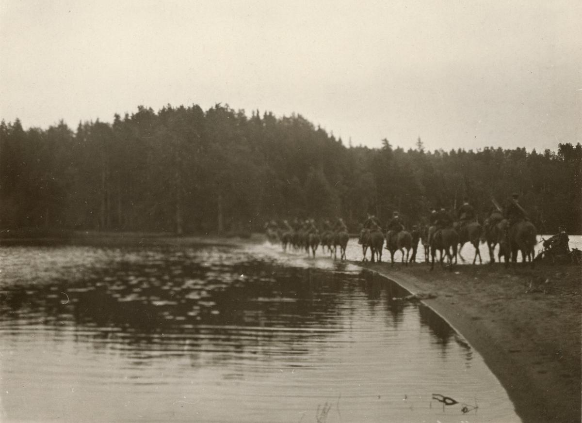 Soldater från Livregementets husarer K 3 till häst korsar en vattenled.