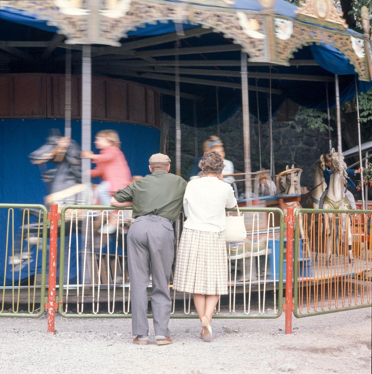 Ett äldre par betraktar barn som åker karusell.