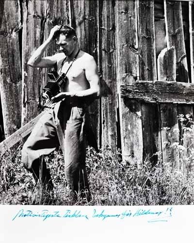 Hilding med bar överkropp och kamera runt halsen, står i gräset framför trävägg.