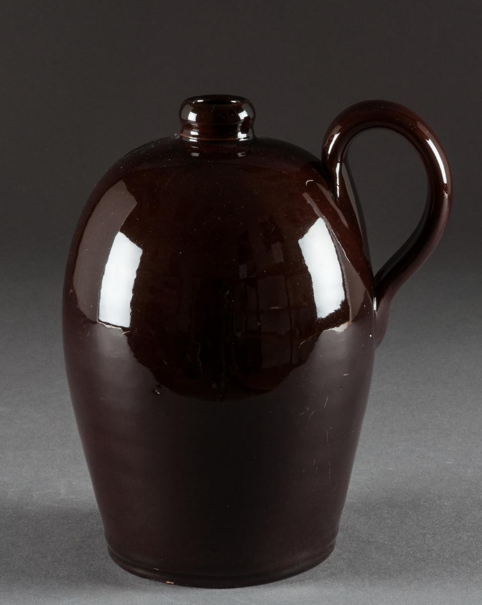 Krus, Bo Fajans, med handtag, mörkbrun glasyr. Höjd 17,2 cm. Prov på fabrikens äldsta tillverkning, 1880-talet.