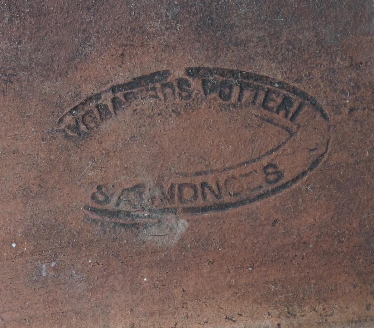 Brennevinskrukke,  Leirtøy, rødbrunt gods, brun blyglassur  med gule ringer. Høy tykkmavet krukke med  2 + 2 + 1 gul ring i øvre halvdel. Smal munning med tykk brem. Stempel: Nygaards Potteri, Sandnes. Stemplet nede ved bunnen, noe utydelig.