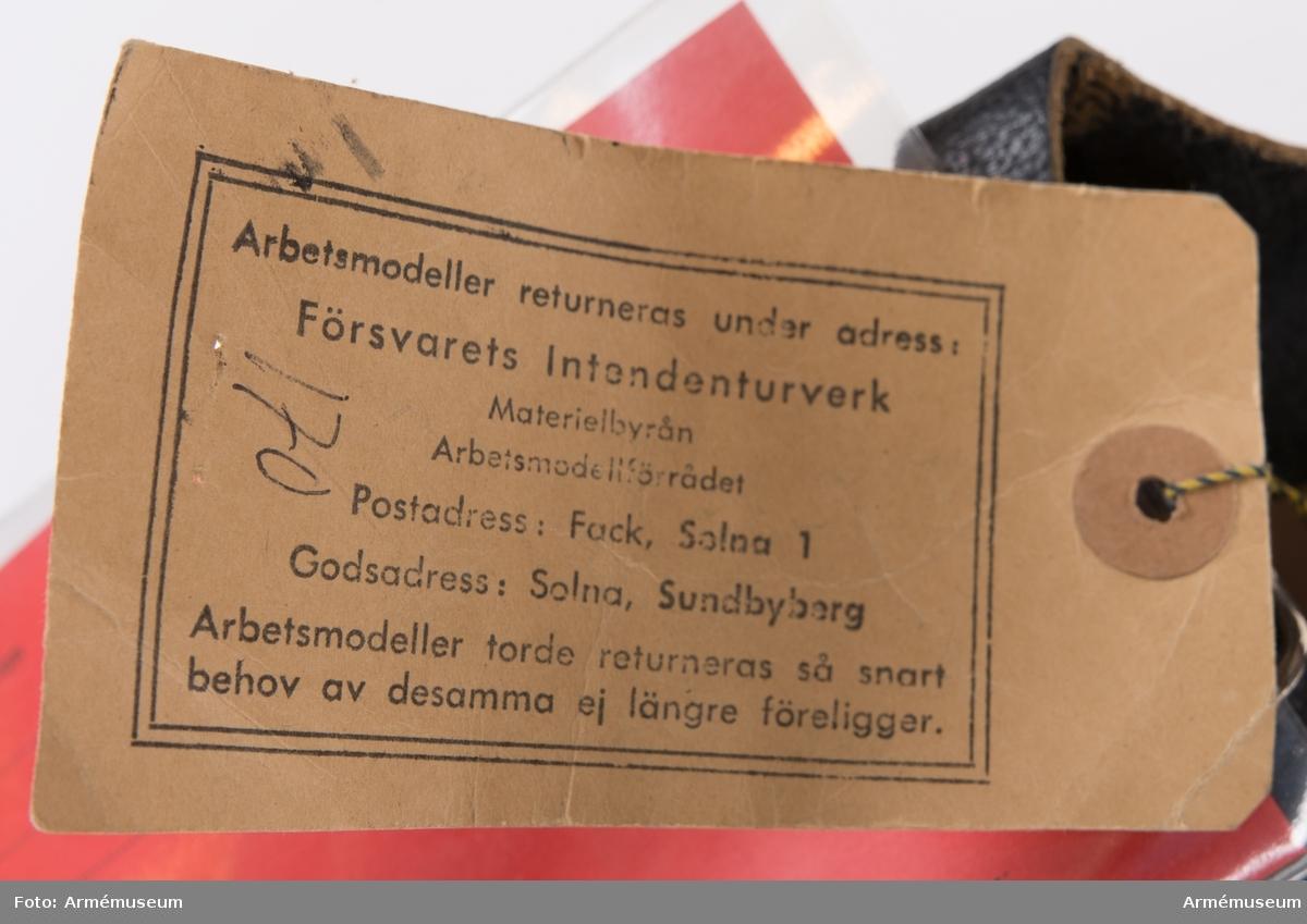 """Toffla med svart ovanläder och lädersula. Hel tå- och hälkappa. Slejf som knäpps med metallspänne. Under sulan och i innersulan är fabriksnamn samt storlek 42 A inpräglat. På sulan finns även tillverkningsåret 1959. Skon har två vidhängande etiketter. Den ena med text: """"Försvarets materielverk. Originalmodell. M 7335-155000-2 Maskintofflor. 1986-04-11. Elisabeth Rönnberg (?) IntT. Göran Olmarks (?) QInt."""" Den andra, äldre, lappen har texten: """"Arbetsmodell för Maskintofflor (M) Solna 2.8.1965. B Olsson Bdir. Mk: (oläslig signatur)"""""""