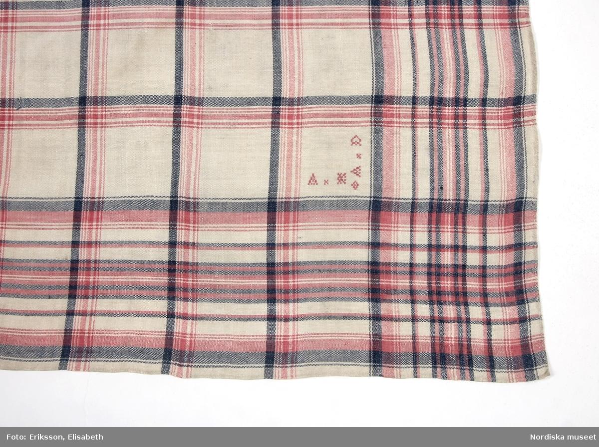 Kvadratiskt halskläde av vitt tuskaftat linne, rutigt i mörkblått lingarn och rosa bomullsgarn. Märkt i 2 av hörnen, i det ena A K A D och i det andra A C A D med rosa bomullsgarn i korssöm. Smala fina handsydda fållar runtom. Datering uppskattad till tidigt 1800-tal men kan även vara något tidigare beroende på när det röda/rosa bomullsgarnet började  användas i bygden. Infört som huvudkläde men vid den tiden användes de i första hand som halskläden, men kunde också knytas utanpå en mössa. I fint skick. /Berit Eldvik 2012-01-18