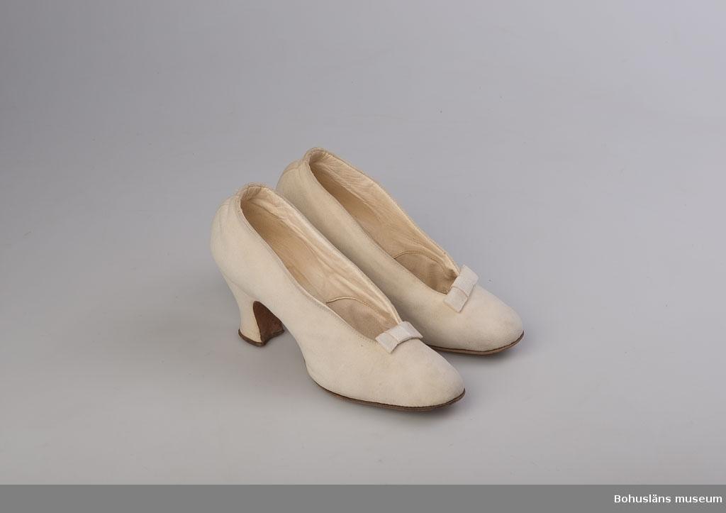 Skor i vit mocka och med lädersula till brudklädsel. Slät yta med rosett av vitt ripsband som enda dekor. Sammanhör med brudklänning; se UM026644 för ytterligare uppgifter.