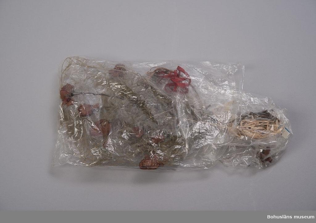 Greta Karlssons brudbukett från bröllopsdagen 30 december 1922. Sju röda rosor och fjädersparris. Buketten instucken och sparad i två plastpåsar av senare datum.  Sammanhör med: UM018551 Skor, UM018591 Brudslöja samt UM018596 Diadem.  Se UM018527