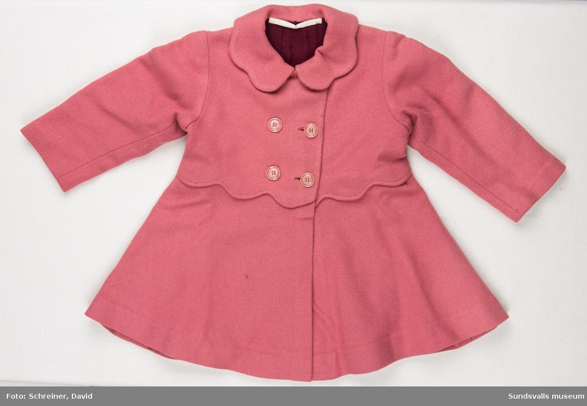 En rosa kappa med dubbelknäppning, Midjan har markerats av en skuren vågformning vilken också återkommer i halskragens utförande. Vinrött foder.
