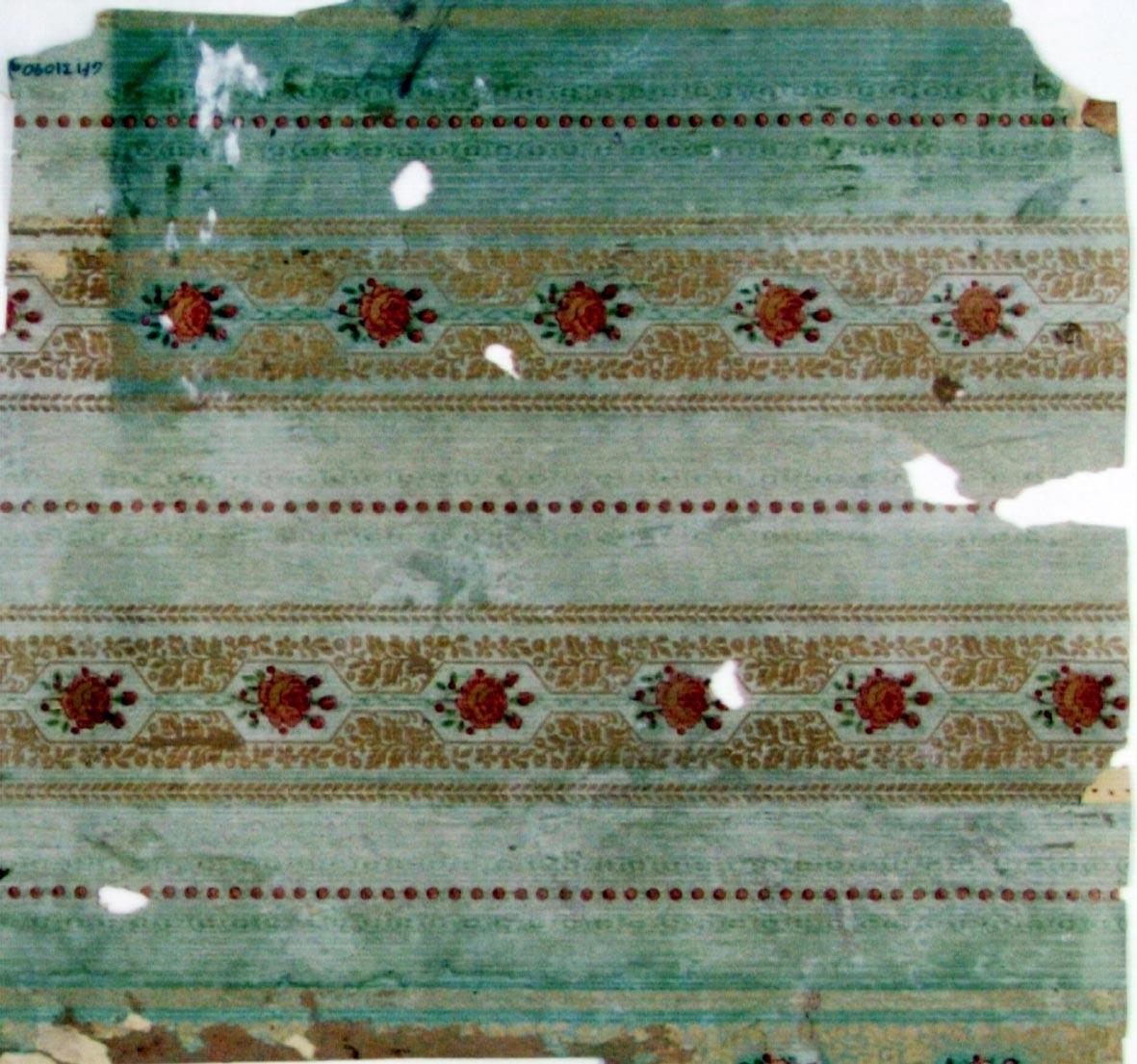 Randmönster med rosor i flerhörniga ornament omväxlande med lodrät pärlstav. Tryck i rött och grönt på en ljusgrön bakgrund.