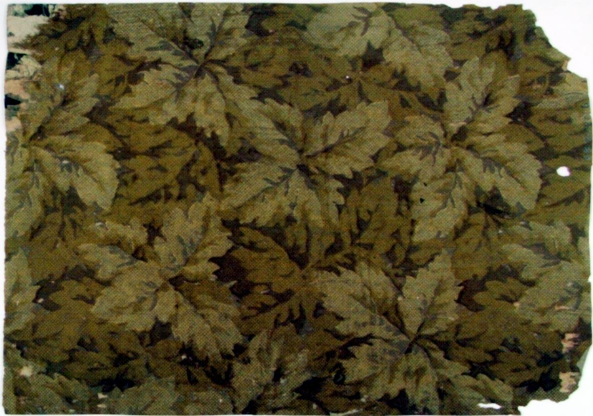 Tätt ytfyllande bladmönster i flera bruna nyanser. Övertryck med snedrutmönster.