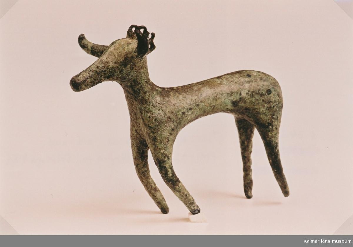 Tjur eller hjortstatyett av brons, kronprydd. Fynd vid arkeologisk undersökning 1991-02.  Höjd 7 cm.