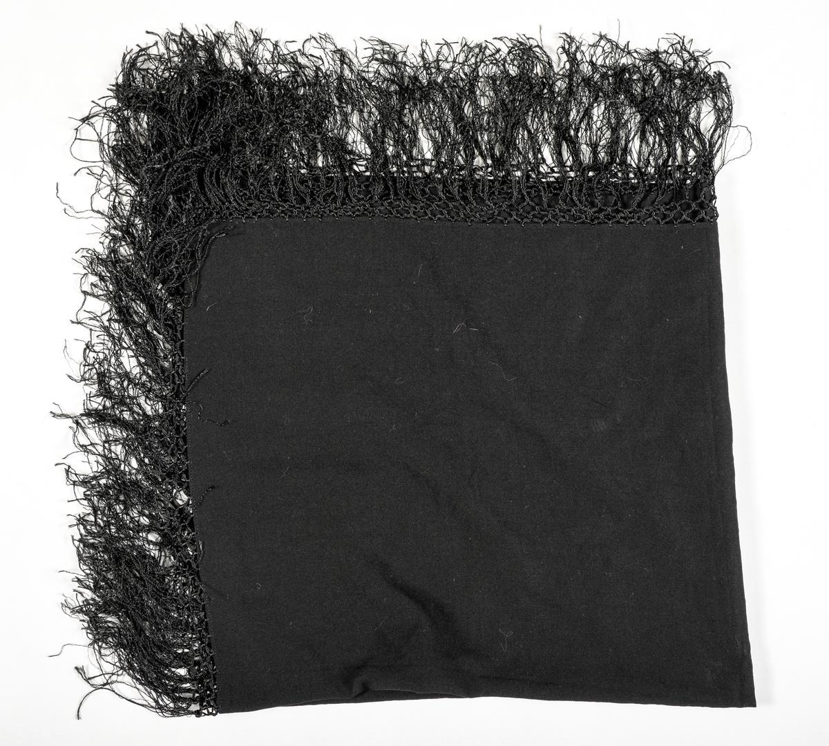 Tørkle i svart ullmusselin. Falda i to sider med maskinsaum. Påsette silkefrynser.