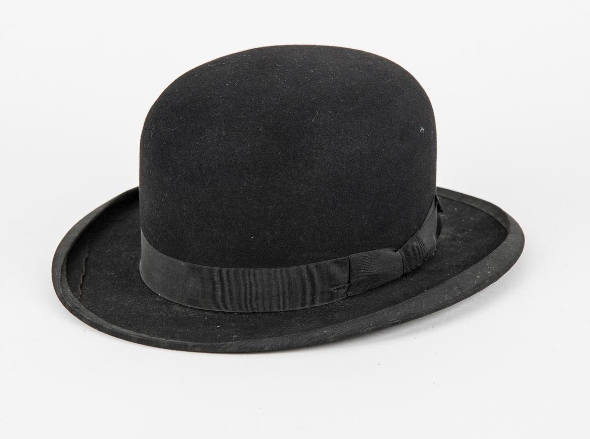 Hatt, rundpullhatt i svart filt. Ripsband rundt pullen og bremkanten. Skinnband på innsida. Fóra med rosa silke.