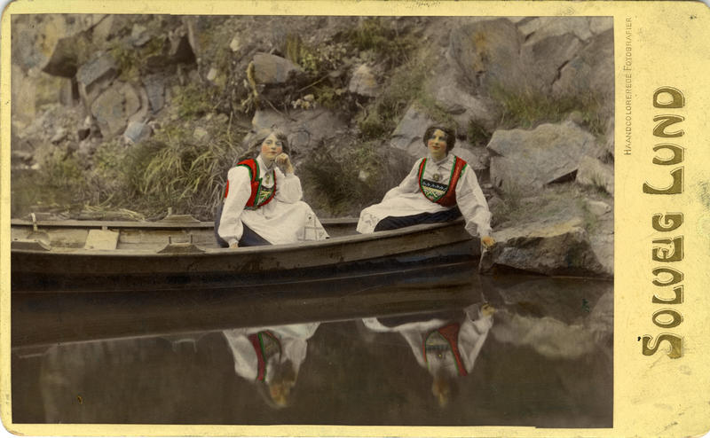 Kolorert fotografi av to kvinner med drakt i pram. 1908. (Foto/Photo)