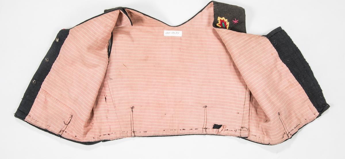 Liv til Valdresbunad i svart heimevove ulltøy, brodert med ullgarn. I opninga er det tre trykknappar. To små snitt framme og to bak. Fóra med stripa rosa kypertvove bomullstøy.