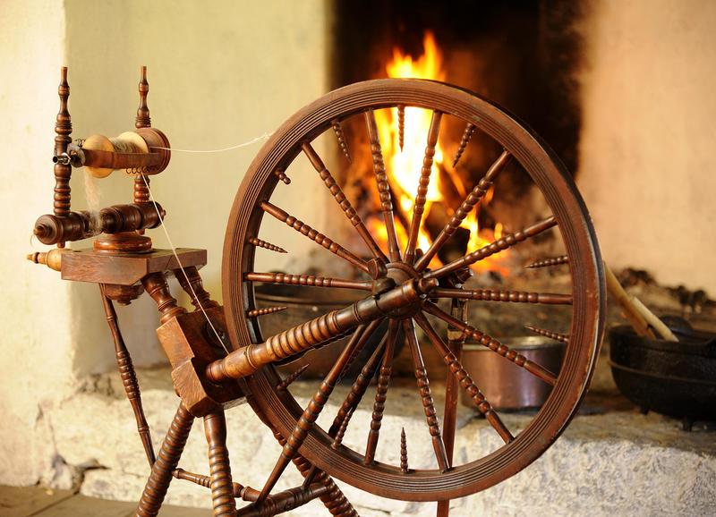 En gammel rokk til å spinne garn på står foran en åpen peis hvor det brenner lunt.