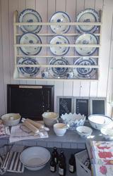 Tallerkenhyle som viser dype og flate tallerkener i hvitt porselen med blå blomsterdekor, kjøkkenhåndklær, boller, kjevler og tavler til å skrive på. (Foto/Photo)
