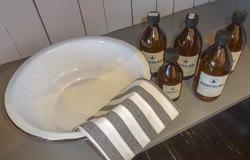 Vaskevannsfat, klut og lokalprodusert såpe som selges i brune glassflasker.