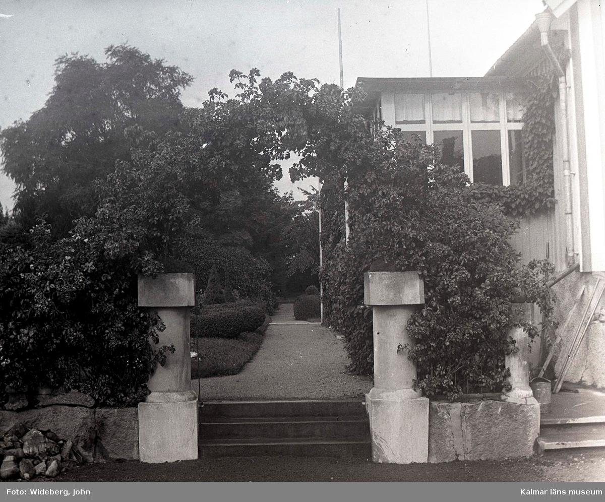 Södra entrén till Widebergs trädgård.  John Wideberg blev tidigt intresserad av trädgårdsanläggningar. Han hade sannolikt hämtat inspiration på resor han gjort till Stockholmsutställningen 1897 och till Göteborg 1923. Han blev också vän med stadsträdgårdsmästaren Haglund i Kalmar. John hade palmer i potatiskällaren under huset och påfåglar, ekorrar och pärlhöns som övervintrade i hönshuset. En papegoja och en sköldpadda fick tillbringa vintrarna inne i köket. Runt trädgården planterade han skyddande häckar. Arbetet påbörjades redan när han var 18 år med att han hämtade åtta granar i skogen, och planterade dem i en ring mitt i trädgården. Dessa finns kvar än idag. I slutet av 1930-talet arrenderades jordbruket ut och John kunde ägna sig på heltid åt trädgården, som blev alltmer av ett besöksmål. John började ta inträde, 25 öre. John utvecklade också sin hobby som tavelmålare och som fotograf. Han tog med sin lådkamera under årens lopp hundratals vackra bilder från trädgården, liksom på vyer, hus och människor i takten. Ca 500 av dessa bilder finns bevarade som glasplåtar, skänkta till Kalmar läns museum.