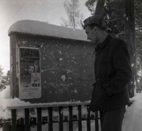 """Vid en snöig anslagstavla längs vägen mot Hudiksvall har en man stannat till och läser intresserat den uppsatta affischen. Året är 1950 och det som annonseras är en visning av """"Tarzan och  kvinnan från havet"""". Mannen, med händerna i fickorna och pälsmössa på huvudet, ler när han ser på affischen."""