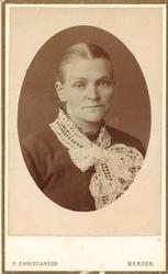 portrettfotografi av kvinne med midtskill, kledd i mørk kjol