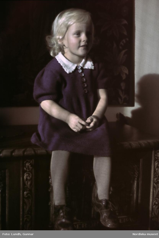 Ett barn i mörk klänning med vit krage och läderskor sitter på en stol.