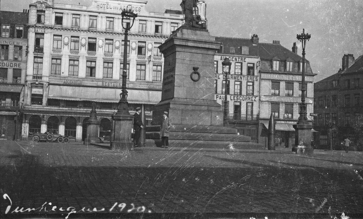 Dunkerque. To menn ved siden av en statue på torget i Dunkerque foran flere større bygninger bla et hotell. Hverdagsfoto.