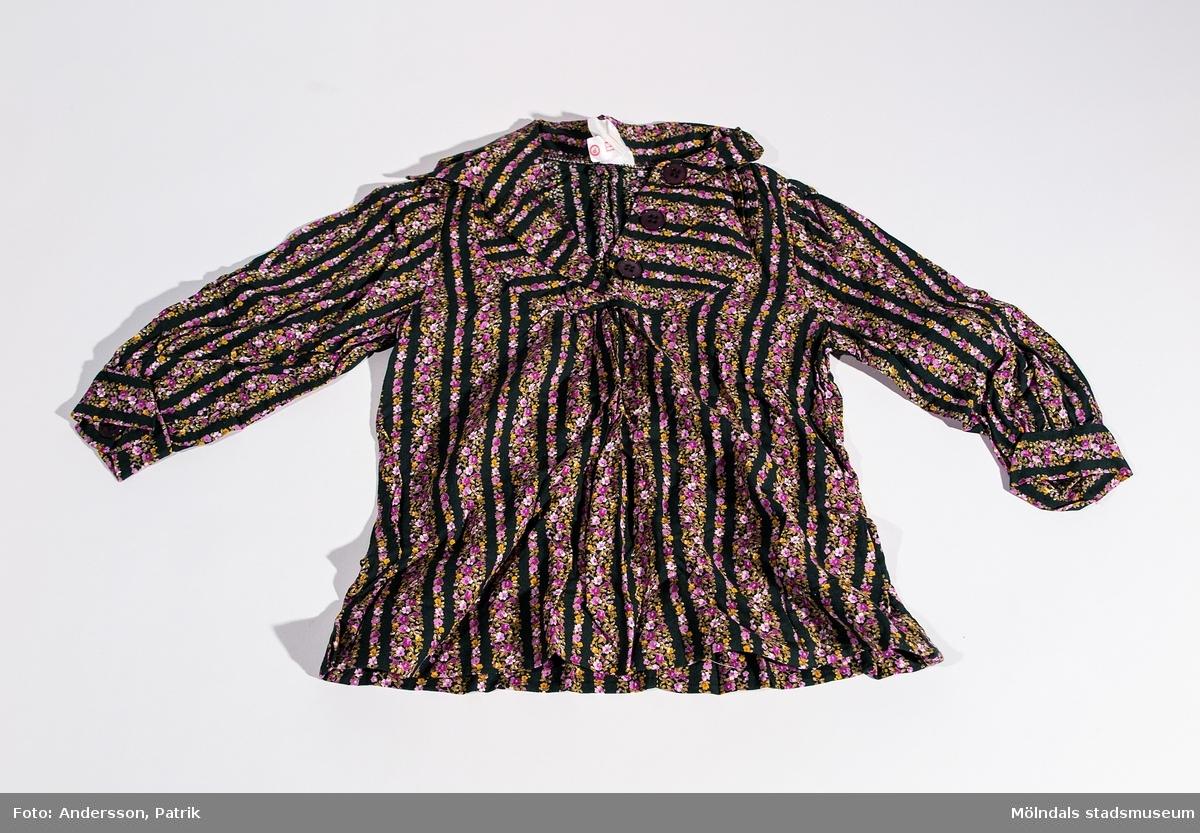 """Klänningen med helsvarta och blommiga ränder. Blommorna går i färgerna orange/brun och lila. Man knäpper klänningen med tre svarta knappar i brösthöjd och uppåt. Det sitter även en svart knapp på varje armmudd. I klänningen finns två lappar fastsydda med tryckt text. På ena lappen står: """"Backafall modell 91"""". På den andra lappen står klänningens tvättråd. """"Karins festklänning i storlek 91 som hon hade på sig på sin 1-årsdag, 1979."""""""
