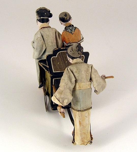 Kinesisk figurgrupp med dragkärra, utskuren i svartmålat trä med två metallhjul. Påklistrade textilier pryder kärran.  Två trästänger diagonalt från kärrans baksida samt under dessa horisontalt metallband med ett stödhjul och ytterst liten yta där en kines står och håller i trästängerna.  Figuren har keramikhuvud och -händer samt är klädd i fotsid dräkt i gröna och bruna pastellfärger.  På kärran sitter ett kinesiskt par med fötterna på rektangulär plattform. Inbyggd mekanism gör kärran självrullande.