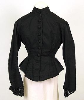 """Enl liggare:  """"Turnyrklänning, dam, bestående av a/ liv och b/ kjol, sidenrips, svart, helfodrad med bomullstyg. 1870-tal. Livet knäppt fram med 6 överklädda knappar. Omsytt. Spetsgarn. å ärmar, tillkommit senare. Kjol utsläppt i midjan. a/ L 61 cm br. över axlar 44 cm. b/ L 128 cm."""""""