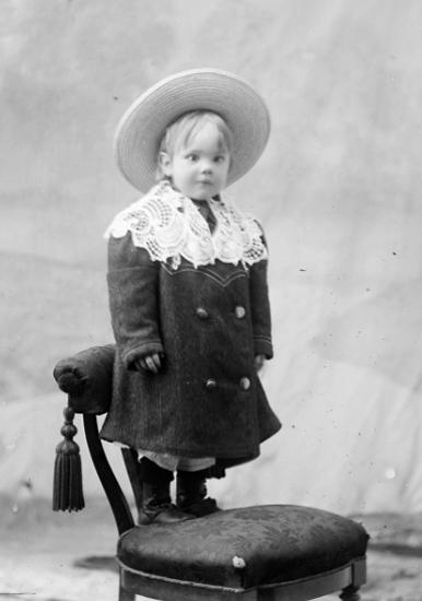 Ateljé. Pojke med halmhatt stående på stol. Fotograf: Ellen