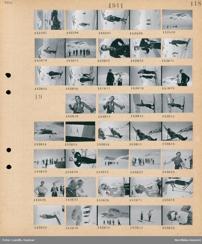 Motiv: (ingen anteckning) ; Kvinnor och män åker skidor i ett snötäckt landskap med fjäll i bakgrunden.  Motiv: (ingen anteckning) ; Kvinnor och män åker skidor i ett snötäckt landskap med fjäll i bakgrunden, ett hus, två soldater i uniform med gevär sitter i solstolar, en kvinna i solglasögon och ansiktskydd.