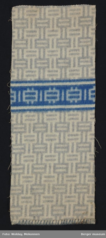 En prøve. Grafisk mønster i grått med en blå stripe med samme mønster. II